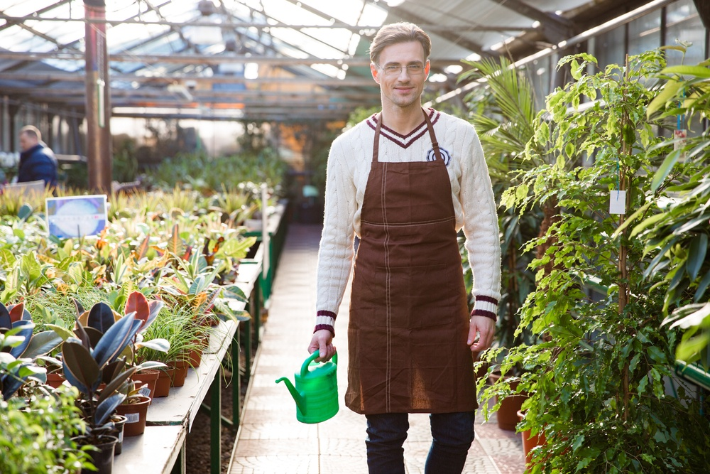 Smiling man gardener in glasses and brown apron standing and holding watering can in orangery.jpeg